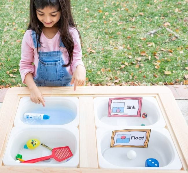 Preschool science student placing objects in bins of water to see if they sink or float
