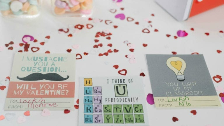 Colorful punny valentines laying on a table covered with mini red hearts