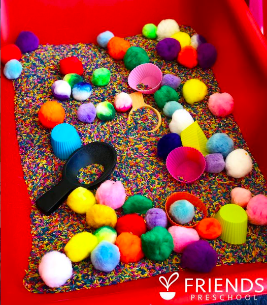 Multicolored pompoms, silicone cupcake liners, rainbow rice and scoops in a sensory table for classroom sensory play