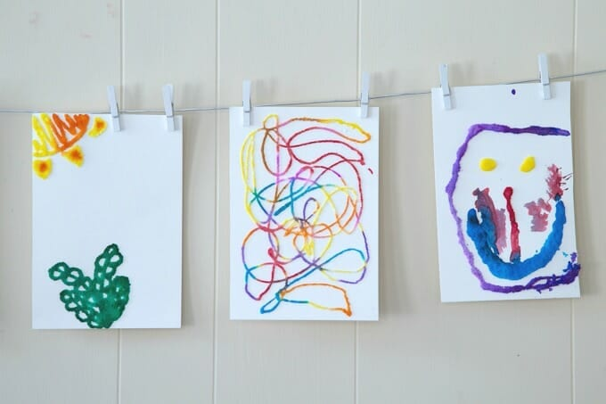 Paintings hanging on a line, made from salt, glue, and paints (Kindergarten Art)