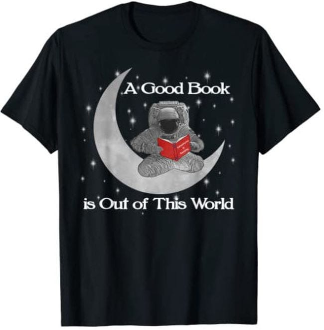 Black t-shirt with picture of astronaut sitting on a crescent moon with a book, text reads A good book is out of this world (Reading Shirts)
