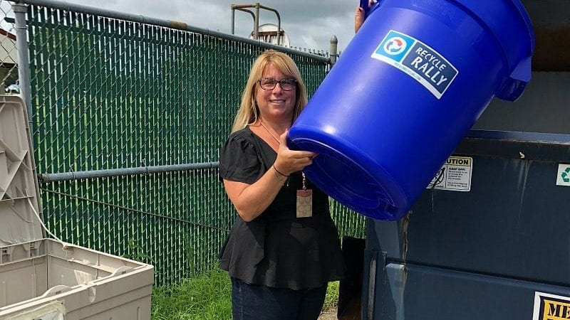 A woman dumping a blue recycling trash can into a dumpster