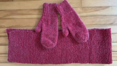 pair of knitted red mittens and scarf on wood floor