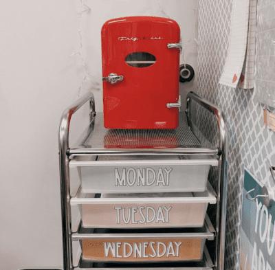 Red mini fridge in classroom on top of drawers