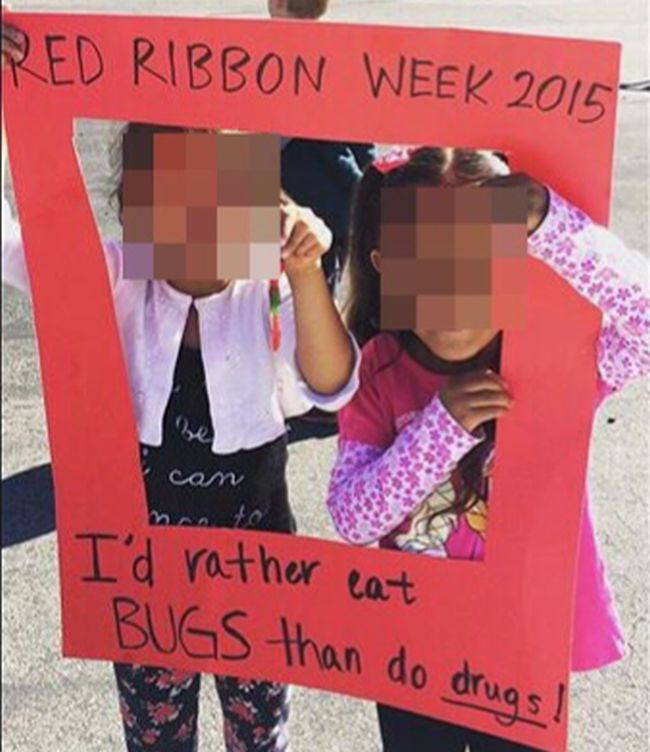 """Students holding a red paper frame saying """"I'd rather eat bugs than do drugs"""""""