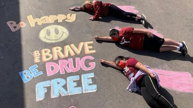 Three students lying by a chalk drawing saying Be happy, be brave, be drug-free (Red Ribbon Week Ideas)