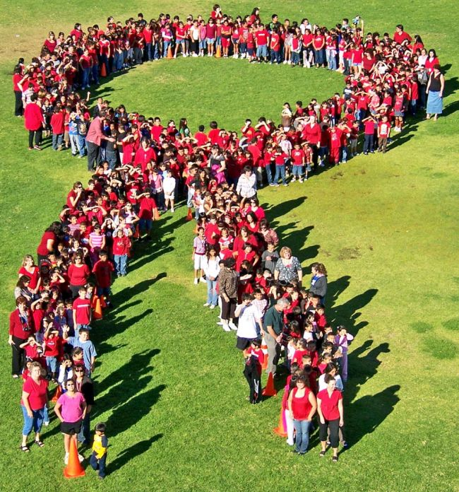 Students and teachers wearing red posing in the shape of a red ribbon, photographed from above (Red Ribbon Week Ideas)