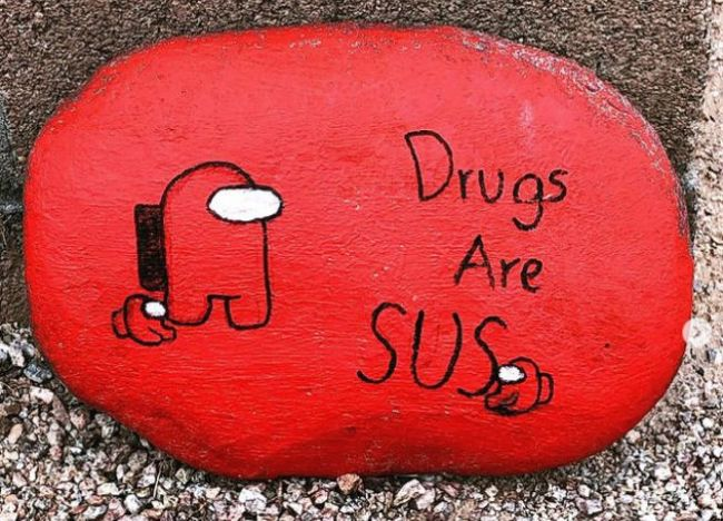 """Small rock painted red saying """"Drugs are SUS"""""""