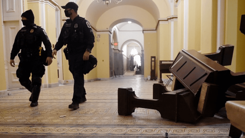Capitol building attack showing security guards walking through hall