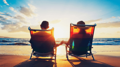 back view of retired couple in lounge chairs at beach watching the sun set after they used the retirement planning checklist