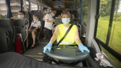 COVID-19. Female bus driver looks at camera confidently while driving the school bus