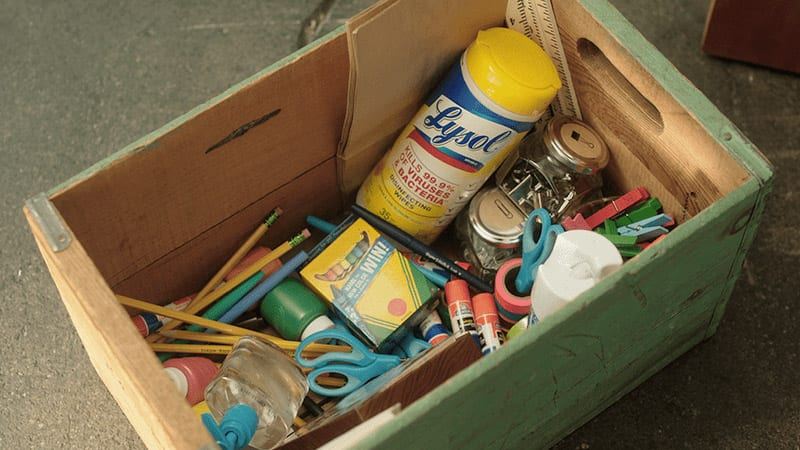 Wooden box with school supplies including Lysol Wipes and crayons