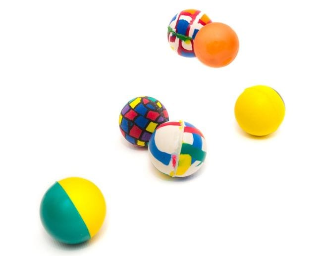 Colorful rubber balls bouncing against a white background
