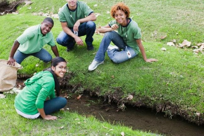 Students examining the water in a ditch in a green field (Science Experiments for High School)