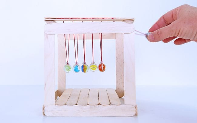 Student swinging the right ball on a DIY Newton's Cradle made of popsicle sticks and marbles