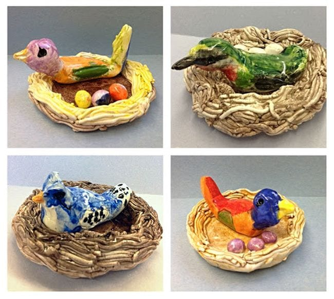 Clay birds in clay nests with eggs