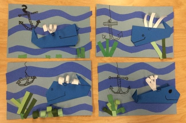 Paper origami whales on a blue construction paper background