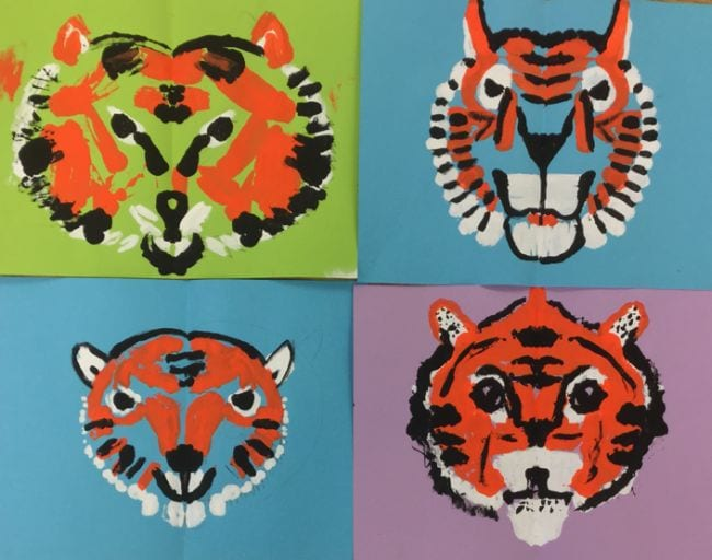 Symmetrical tiger faces printed with paint on colored backgrounds (Second Grade Art)