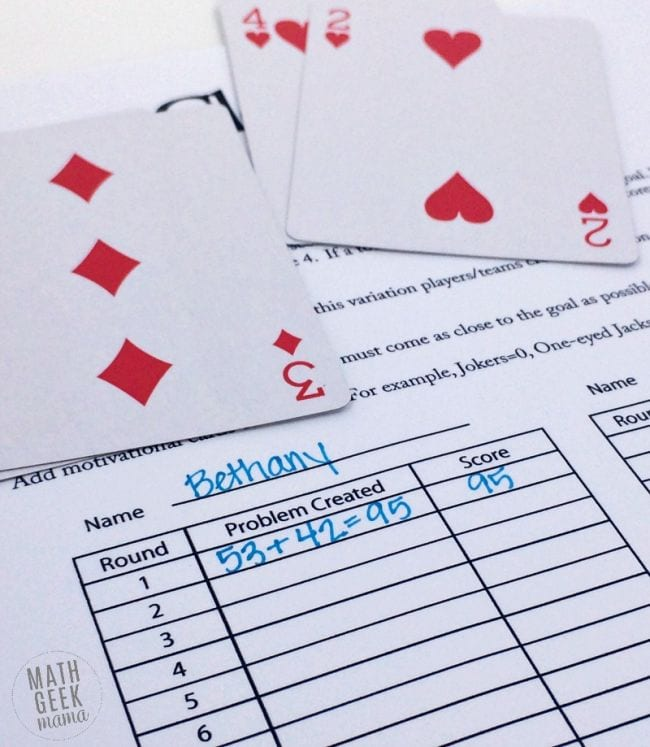 Four playing cards and a printed worksheet with equations and scores