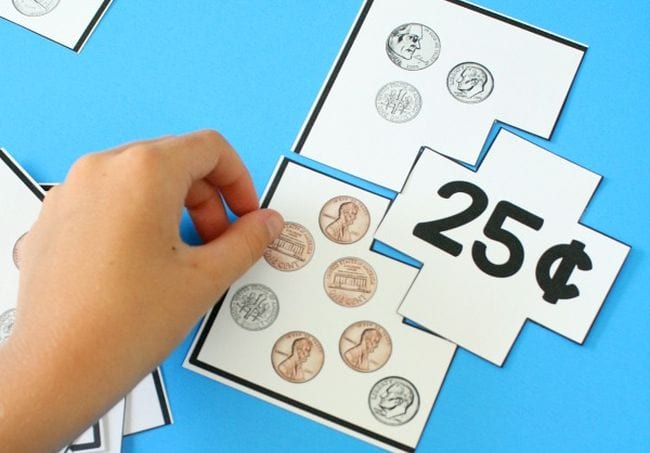 Second grade math student matching coin pictures with a card labeled 25 cents