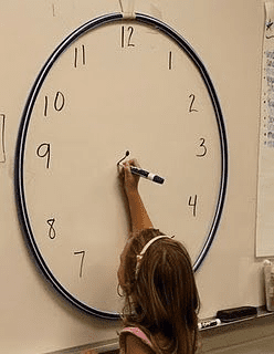Second grader drawing clock on whiteboard.