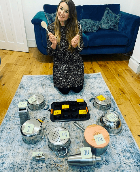 A teacher holding a wooden spoon in front of sticky notes with sight words stuck to various pots and pans and other metal objects