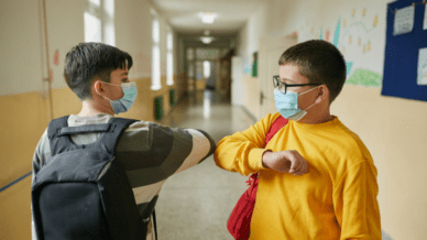 two elementary school boys tapping elbows in the hallway at school to build resilience in students