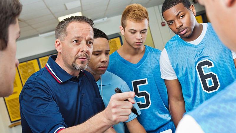 High school coach instructing basketball players in locker room