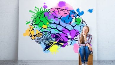 Young woman sitting in concrete room with colorful brain sketch on banner. Creative thinking concept.