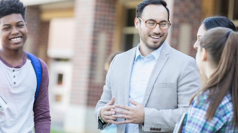 Cheerful high school teacher talks with students