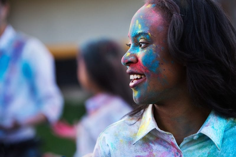 young African American girl with colorful paint on her face - motivating students