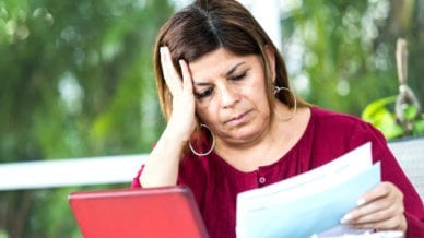 A mature hispanic woman is sitting at the dining table using her tablet to sort her household bills online.She is looking glum as she struggles to sort the family finances. She is holding an invoice .The tablet is surrounded by various bills and debt letters
