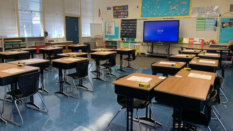 Socially-distanced classroom layouts with chairs staggered around classroom.
