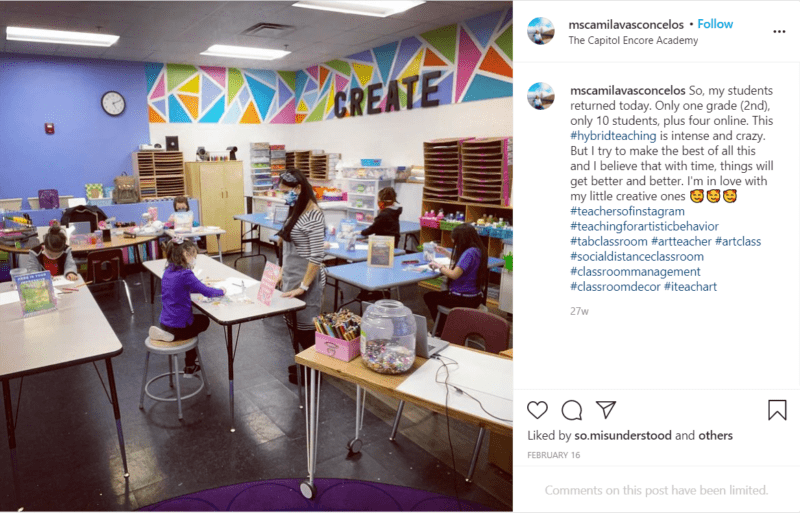 Students in a colorful art classroom with desks in socially-distanced seating arrangements