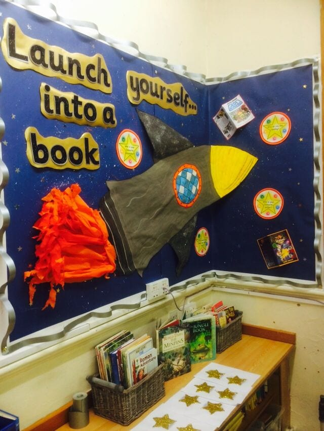 Classroom library corner decorated with dark blue walls and space theme