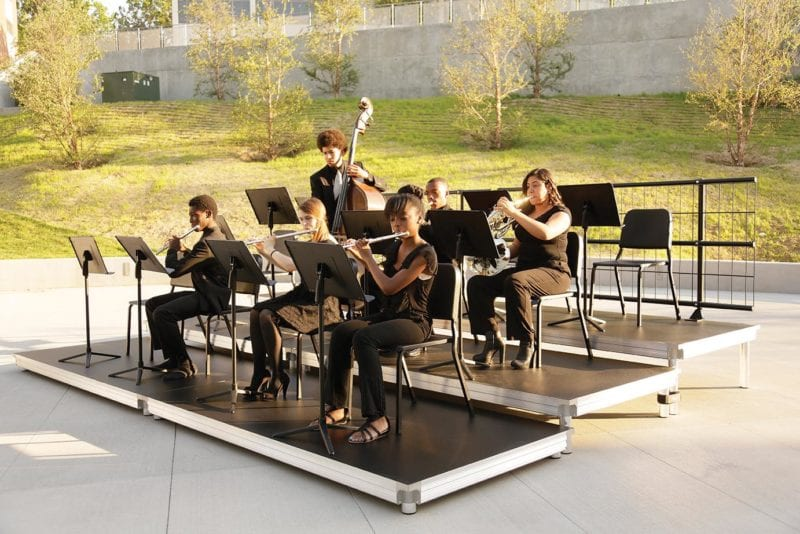 6 students playing instruments outside on risers
