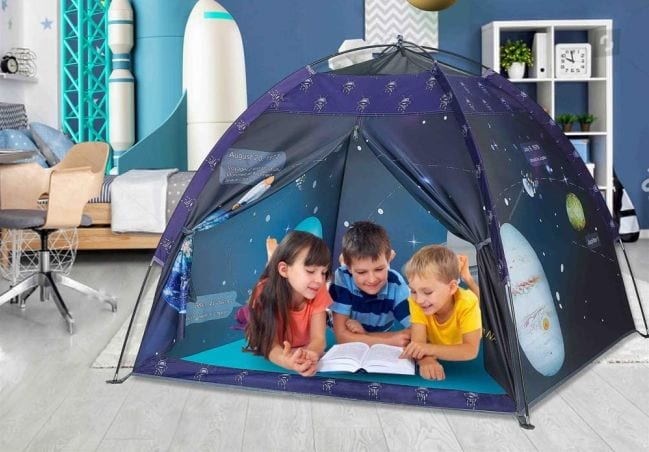 Three kids playing in a space themed tent in the living room