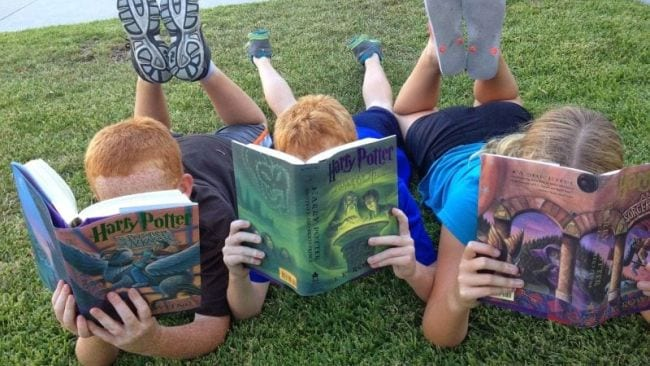 Three kids lying on the grass on their stomachs reading Harry Potter Books (Spring Break Activities)