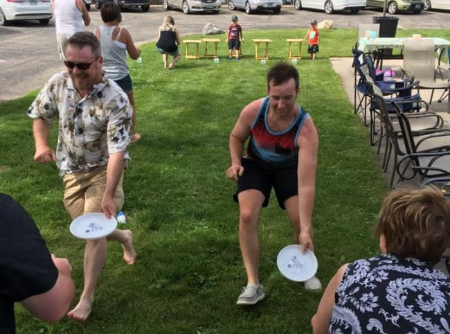 People running with Frisbees full of water while others watch (Staycation Activities)