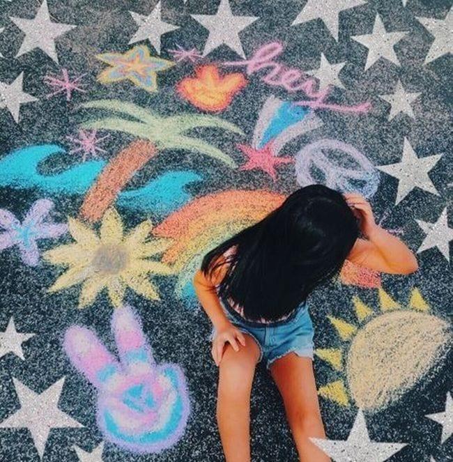 Child sitting among sidewalk chalk drawings of palm tree, rainbow, sunshine, and more