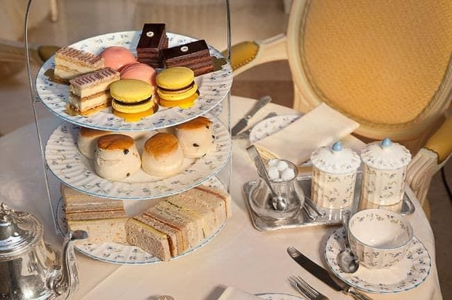 Teapot, teacups, and cake stand with treats on a table (Staycation Activities)