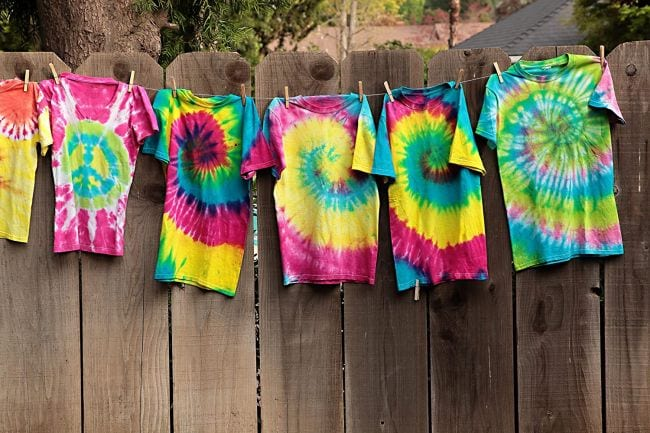 Row of tie dyed shirts hanging on a fence (Spring Break Activities)