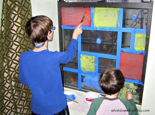 Two children painting colorful squares on a taped-off window