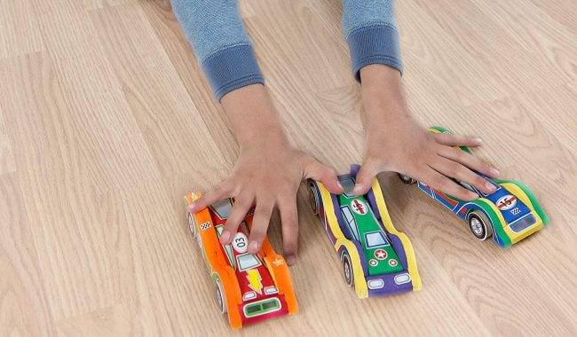 Child racing three colorful wood cars along the floor (Spring Break Activities)