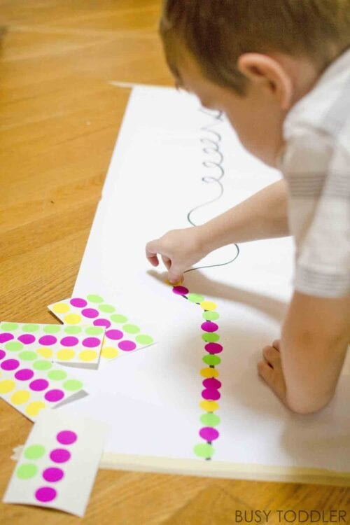 Child placing colorful stickers along a printed line