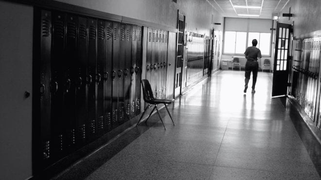 Black and white photo of a teacher in a hallway with lockers--let's stop teacher blame
