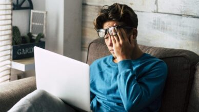 Asian man rubbing eyes in front of laptop pandemic neurological changes