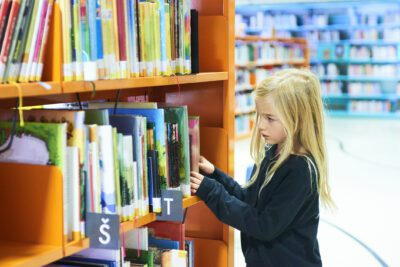 Child girls in library choosing a book