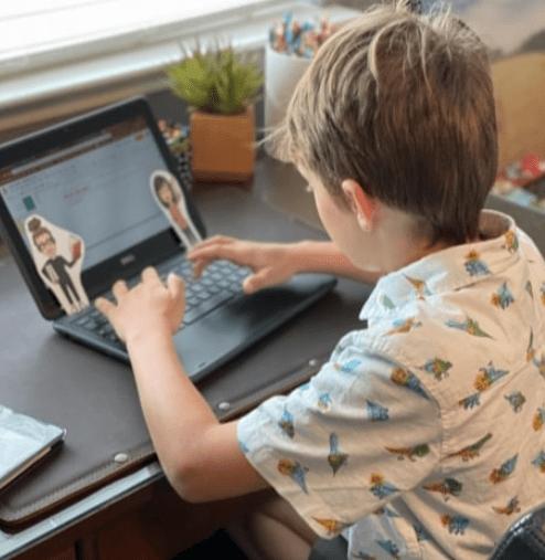 Student props teacher Flat Stanley up against laptop