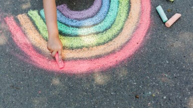 Student draws a rainbow with colored chalk on the asphalt. Child drawings paintings concept. Education and arts, be creative when back to school